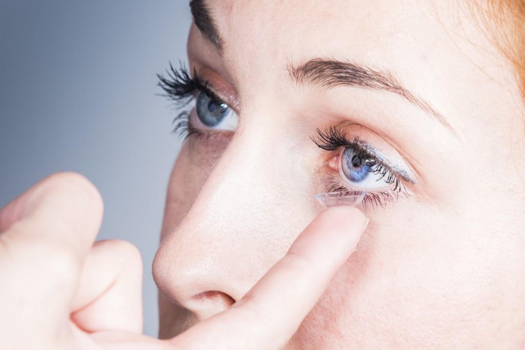 Young woman puts a contact lens